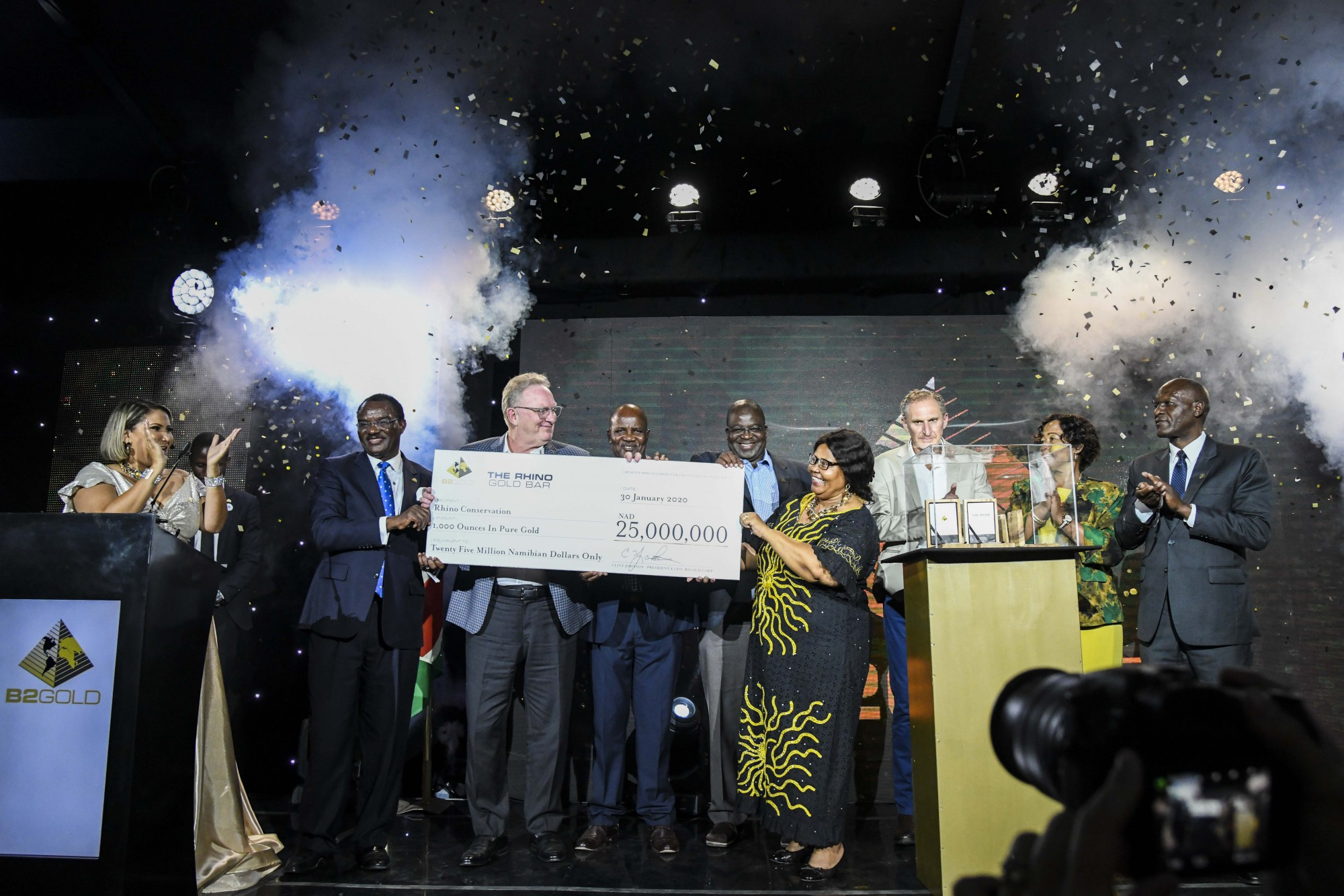 Clive Johnson (President, CEO & Director, B2Gold Corp.) handing a cheque of NAD $25,000,000 (approx. USD $1,500,000)  to various beneficiaries  From left to right: Dr. Leake Hangala ( Director, B2Gold Namibia Proprietary Limited), Clive Johnson, Simson Uri-Khob (CEO, Save the Rhino Trust), John Kasaona (Executive Director, Integrated Rural Development and Nature Conservation), Honorable Bernadette Jagger (Deputy Minister of Environment and Tourism), Mark Dawe (Country Manager and Managing Director – Namibia, B2Gold Corp.), Inge Zaamwani-Kamwi (Adviser to the President of the Republic of Namibia, Dr Hage Geingob) and Tom Alweendo (Minister of Mines and Energy)